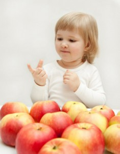 A child counting apples.
