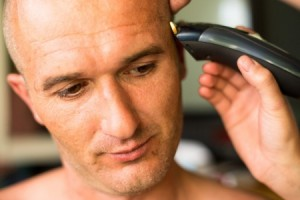 A man shaving his head.