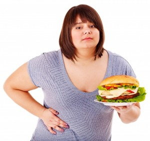 a fat girl holding her side with one hand and a plate filled with food in the other hand